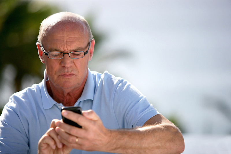 Senior man sending text message